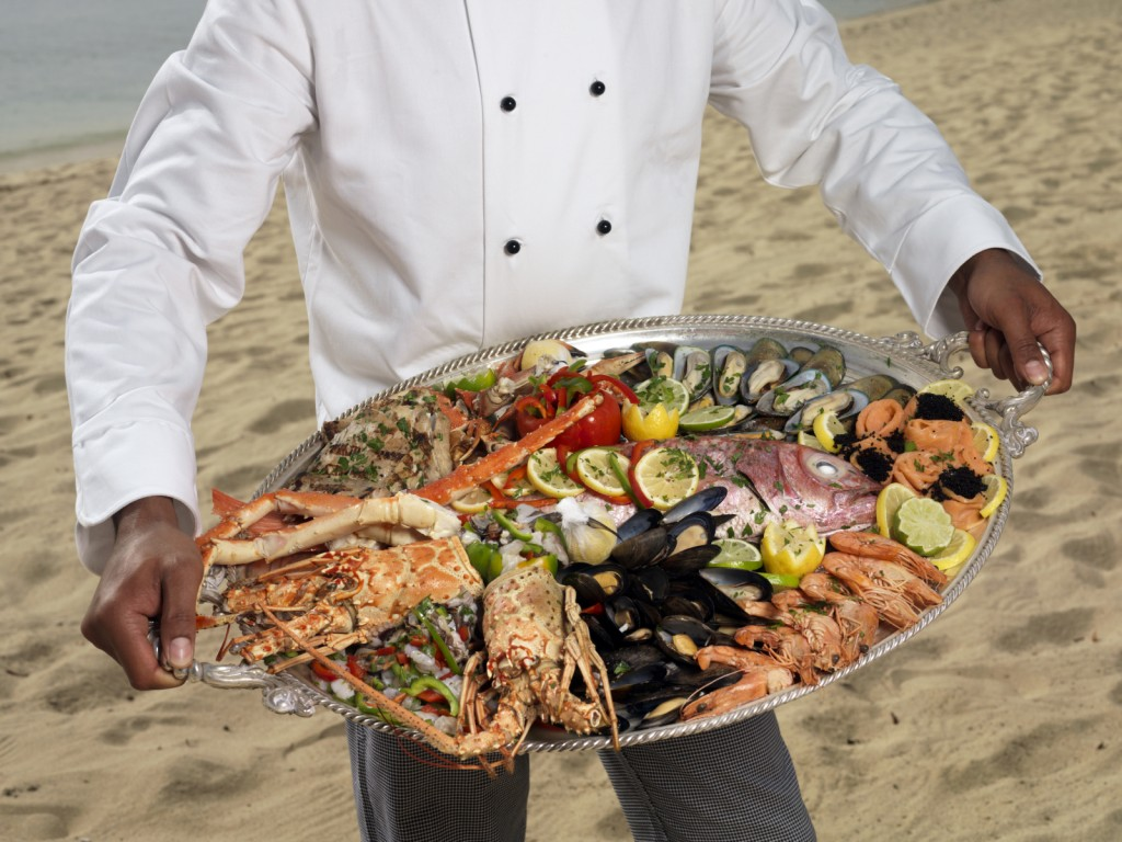 Chef holding a platter of fresh seafood istock